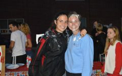 Junior Jen OConnor and  senior Abbie Houck pose after getting pied at Class Officer Homecoming carnival booth.