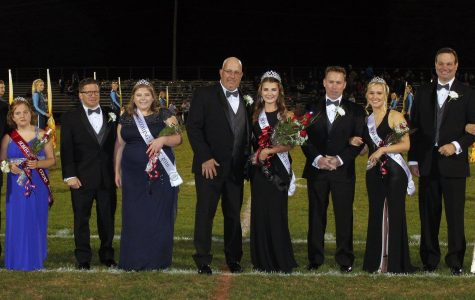 This year's Homecoming court female nominees walk the field with their fathers during halftime at the game.