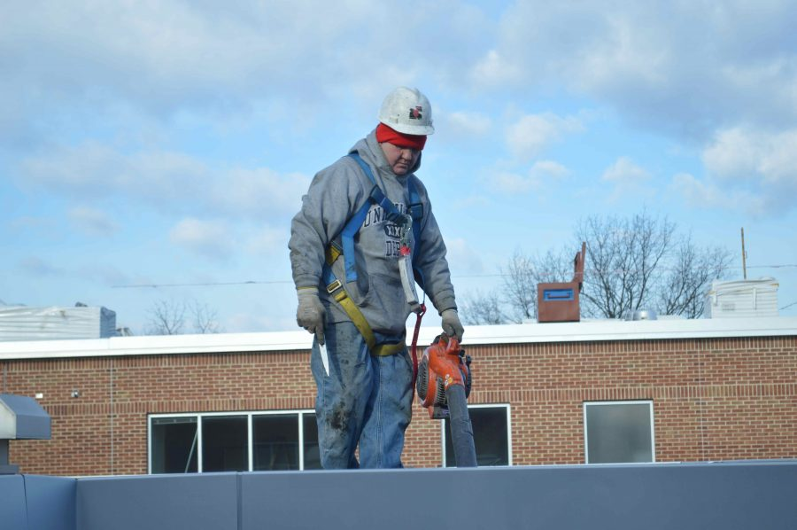 A worker stands on the roof outside the 800s hallway as construction continues at BASH.