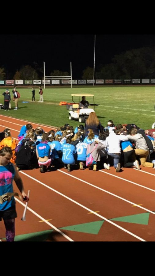 Students gather for a prayer before the Powder Puff game for Junior Morgan Strauss, who had been severely injured in a car crash the day before.