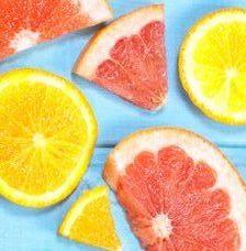 Mix fresh sliced orange, lemon and grapefruit on blue wooden table
