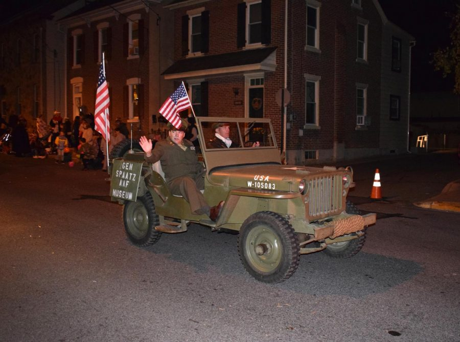A reenactor posing as Boyertown native Gen. Carl Spaatz rides the parade on a WWII vintage Jeep.