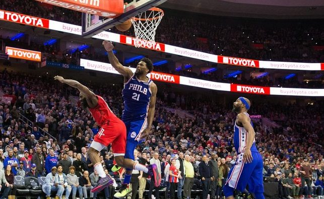 Sixers' Joel Embiid viciously blocks Rockets' James Harden as Sixers' Corey Brewer looks on.