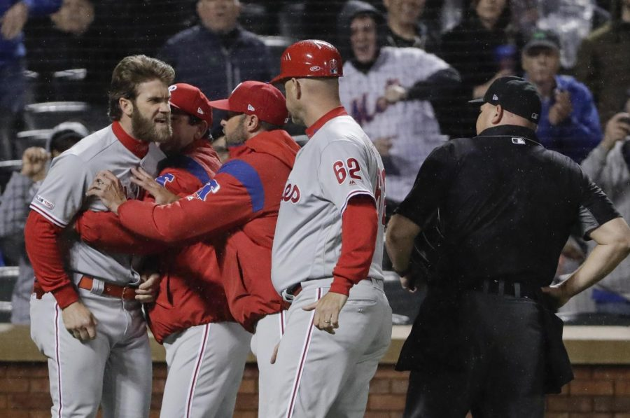 Phillies' Bryce Harper has to be restrained by coaches and manager Gabe Kapler after being ejected from the Phillies' 5-1 loss to the Mets on Monday night.