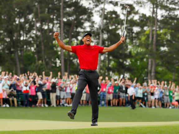 Tiger Woods of the United celebrates after sinking his putt on the 18th green to win.