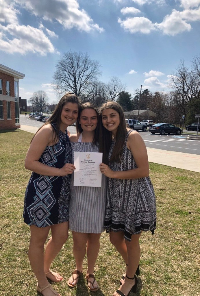 Juniors Emily Hillegas, Shannon Ludwig and Maddi Monka celebrate after the NHS induction.