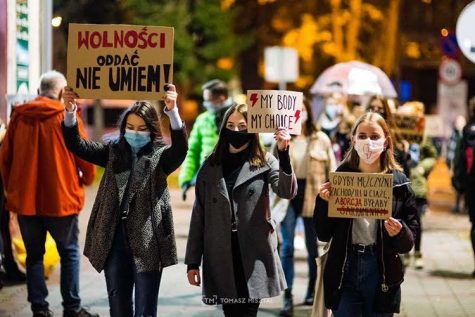 Kinga Kaliszczak (right) and her friends hold up signs while participating in a protest against a nationwide abortion ban