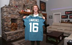 Clemson quarterback, Trevor Lawrence holds up his draft jersey after getting selected first overall by the Jacksonville Jaguars. Trevor celebrated with his family including his new wife, Marissa Mowry, and parents Jeremy and Amanda Lawrence from his home. They opted to watch the draft from his home due to Covid-19. Photo by Logan Bowles/NFL